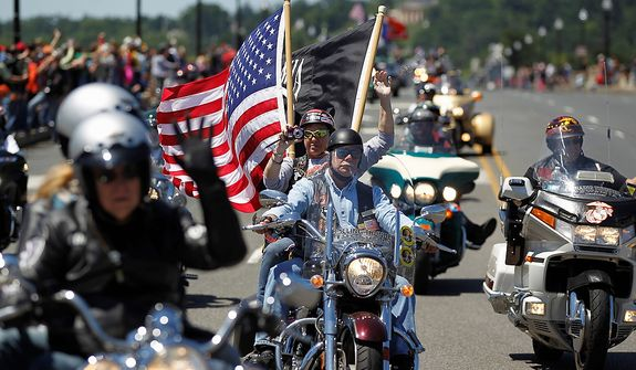 "Motorcycles drive over the Memorial Bridge during the annual Rolling Thunder ""Ride for Freedom"" parade ahead of Memorial Day in Washington, Sunday, May 26, 2013. (AP Photo/Molly Riley)"