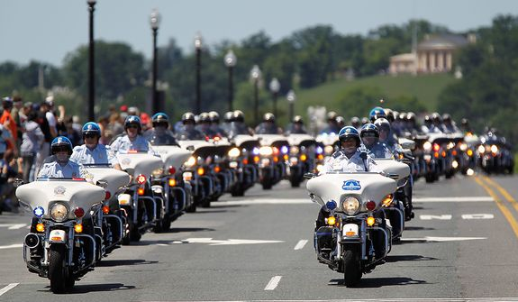 "Police officers lead the way for the motorcyclists, many of whom are veterans, across the Memorial Bridge into Washington during the annual Rolling Thunder ""Ride for Freedom"" parade Sunday, May 26, 2013, ahead of Memorial Day celebration in Washington. (AP Photo/Molly Riley)"