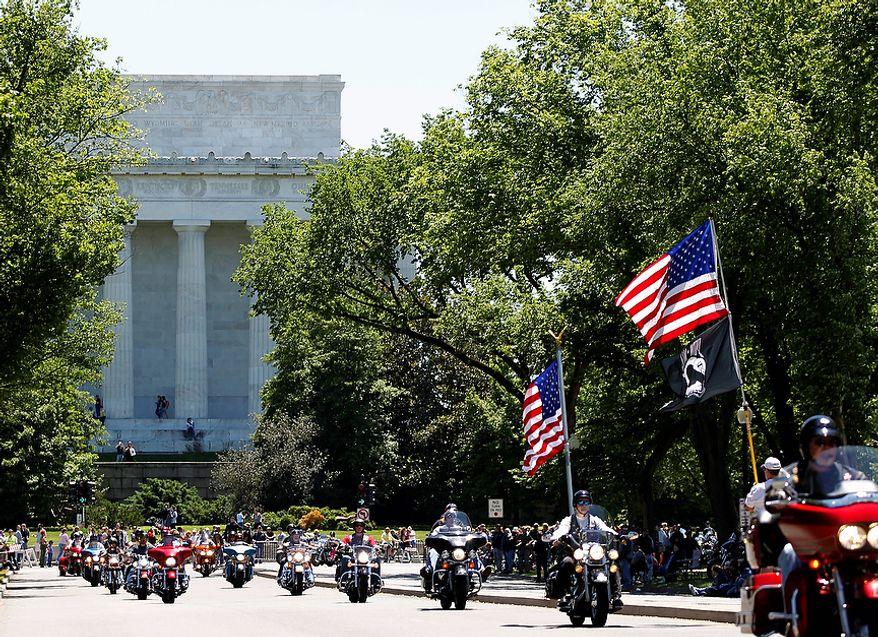 "Motorcycles ride near the Lincoln Memorial during the annual Rolling Thunder ""Ride for Freedom"" parade ahead of Memorial Day in Washington, Sunday, May 26, 2013. (AP Photo/Molly Riley)"