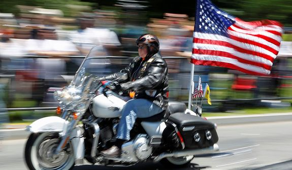 "A motorcycle participates in the annual Rolling Thunder ""Ride for Freedom"" ahead of Memorial Day in Washington, Sunday, May 26, 2013. (AP Photo/Molly Riley)"