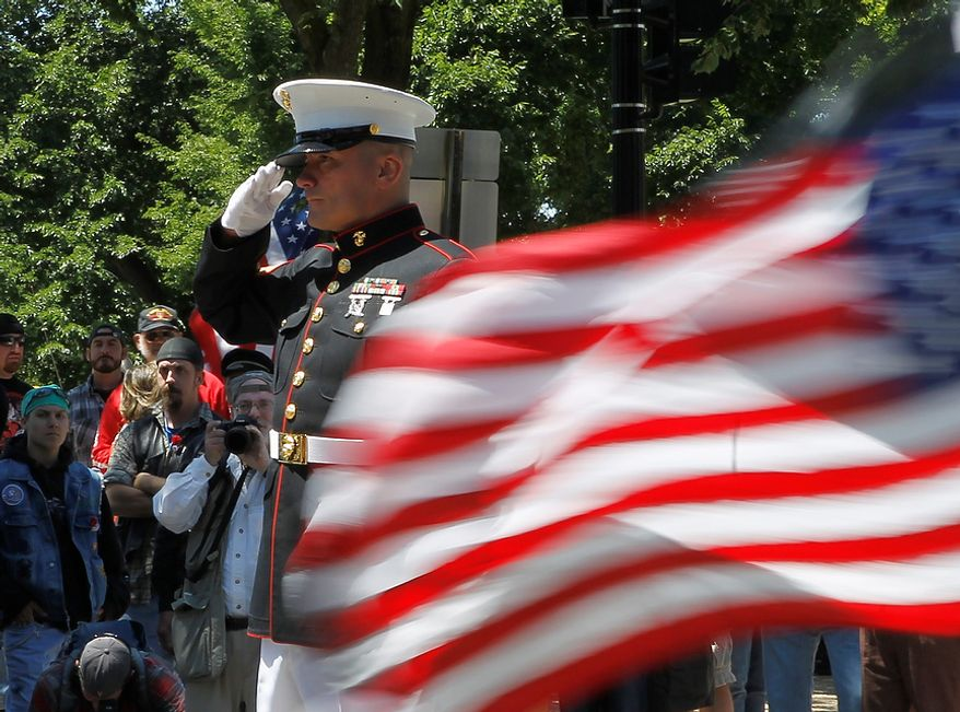 """Motorcycles drive past Marine veteran retired Staff Sargent Tim Chambers as he salutes, during the annual Rolling Thunder """"Ride for Freedom"""" parade ahead of Memorial Day in Washington, Sunday, May 26, 2013. (AP Photo/Molly Riley)"""