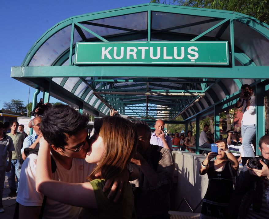 A young Turkish couple kiss to protest subway officials' harassment of a couple for kissing in public last week, at a subway stop in Ankara, Turkey, on Saturday, May 25, 2013. (AP Photo)