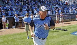 North Carolina head coach Mike Fox takes the field to accept the championship trophy following Carolina's 4-1 win over Virginia Tech in an Atlantic Coast Conference NCAA college baseball game on Sunday, May 26, 2013, in Durham, N.C. (AP Photo/Karl B DeBlaker)