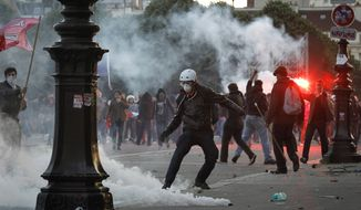 Anti-gay marriage demonstrators face riot police, not seen, while tear-gas canisters smoke during clashes in Paris, France, Sunday, May 26, 2013. Tens of thousands of people protested against France's new gay marriage law in central Paris on Sunday. (AP Photo/Laurent Cipriani)