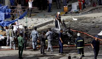 Security forces inspect the scene of a car bomb attack in the Baghdad, Iraq, Monday, May 27, 2013. A parked car bomb explosion in the busy commercial Sadoun Street in central Baghdad killed and wounded scores of people, police said. (AP Photo/Khalid Mohammed)