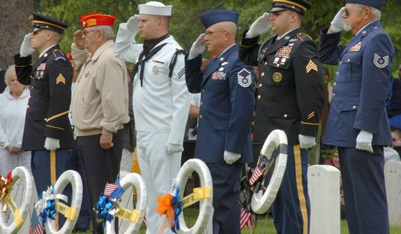 Armed Forces members salute after placing wreaths for the various branches of service during the Memorial Day program Monday, May 27, 2013, at Marion National Cemetery in Marion, Ind. (AP Photo/Chronicle-Tribune, Jeff Morehead)