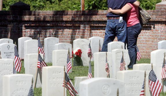 Richard Spence, Jr. and his sister Melissa Spence hug at their father, Richard Spence Sr.'s gravesite at the National Cemetery in New Bern, N.C., on Monday, May 27, 2013. (AP Photo/New Bern Sun Journal, Byron Holland)