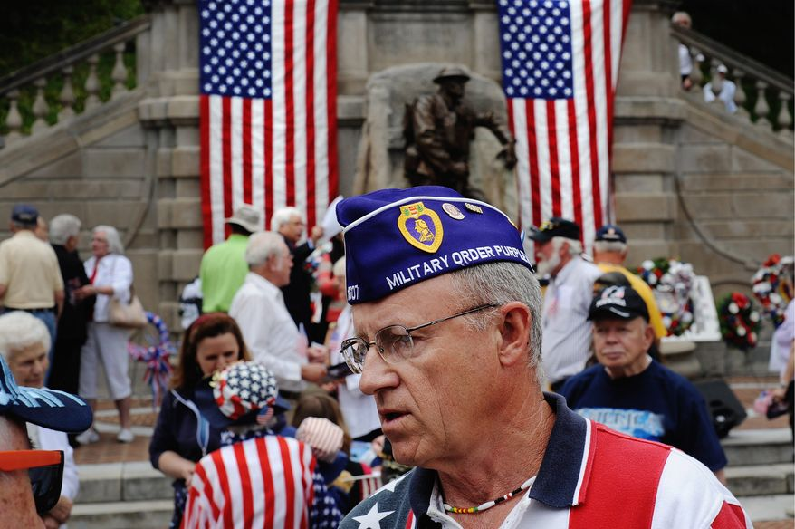 Gary Witt, a two-time Purple Heart recipient for his service in Vietnam during 1968-69 with the Marines, remains at Monument Terrace following the Memorial Day observance to converse with people in the crowd Monday, May 27, 2013 in Lynchburg, Va.  (AP Photo/News & Daily Advance, Sam O'Keefe\)