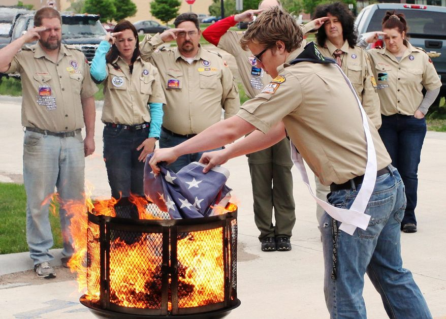 Cooper McCormick of Boy Scout Troop 13 from St. Mary's Catholic Church places an American flag in the fire Monday, May 27, 2013, during a Memorial Day flag retirement ceremony at Sugarloaf Assisted Living in Winona, Minn. The troop retired nine American flags from the community by burning them in a ceremonial fire and later burying the ashes. (AP Photo/Winona Daily News, Andrew Link)
