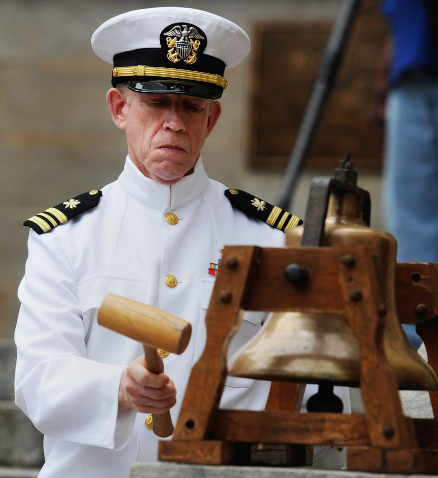U.S. Navy veteran Paul Webb strikes the bell throughout the Memorial Day service, in Lynchburg, VA., Monday, May 27, 2013. (AP Photo/News & Daily Advance, Sam O'Keefe\)