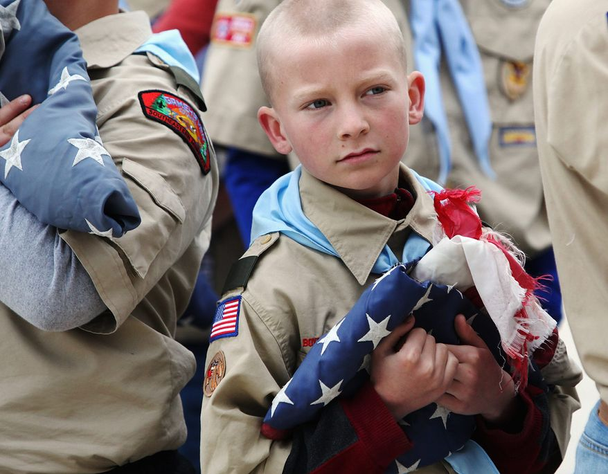 Jeremy Rivers of Boy Scout Troop 13 from St. Mary's Catholic Church holds a tattered American flag Monday, May 27, 2013, during a Memorial Day flag retirement ceremony at Sugarloaf Assisted Living in Winona, Minn. The troop retired nine American flags from the community by burning them in a ceremonial fire and later burying the ashes. (AP Photo/Winona Daily News, Andrew Link) MANDATORY CREDIT