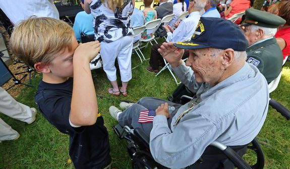 """Eight-year-old Jackson Turman of Woodstock, Ga., gives WWII Navy Veteran and Vietnam Veteran Frank Coleman, 85, Roswell, a salute during the """"Roswell Remembers"""" Memorial Day military ceremony at city hall on Monday, May 27, 2013, in Roswell, Ga. Mr. Coleman returned the salute and gave the young man a hug. Jackson was attending the Memorial Day service with his grandfather Russ Johnson, of Roswell, who is a Marine Vietnam veteran.  (AP Photo/Atlanta Journal Constitution, Curtis Compton)"""