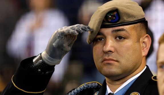 U.S. Army Sgt. Leroy Petry, who lost his right hand in 2008 while serving in Afghanistan, salutes as the flag is displayed prior to a Memorial Day baseball game between the San Diego Padres and the Seattle Mariners, Monday, May 27, 2013, in Seattle. (AP Photo/Ted S. Warren)