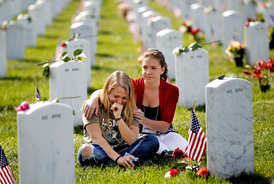 The White House has signed onto a measure that restores the $100,000 death benefit given to families of military members killed in action. During the course of the government shutdown, the payment was withheld from several families who lost loved ones in recent days. In this photo, Heidi Heming, 27 yrs-old, left, of Chattanooga, Tenn.  is comforted by volunteer Marina Clifford, 12 yrs-old, while visiting a loved one's gravesite at Section 60 on Memorial Day at Arlington National Cemetery in Arlington, Virginia, Monday, May 27, 2013.   (AP Photo/Molly Riley)