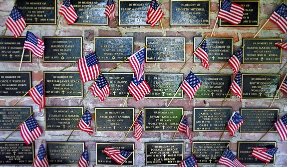 American flags are placed on placards honoring fallen soldiers on a wall at the the Los Angeles National Cemetery during the Memorial Day Service on Monday May 27, 2013. (AP Photo/Richard Vogel)