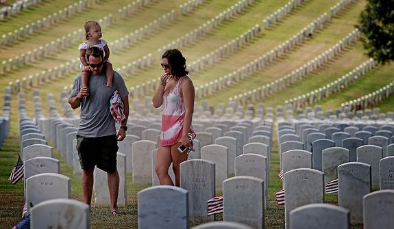 Visitors look over military gravestones  on Memorial Day at Ft Rosecrans National Cemetary in San Diego on Monday, May 27, 2013. (AP Photo/Sandy Huffaker)