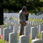 A soldier places roses on grave stones at Section 60 on Memorial Day at Arlington National Cemetery in Arlington, Virginia, Monday, May 27, 2013. Iraq and Afghanistan war veterans are buried in Section 60. (AP Photo/Molly Riley)