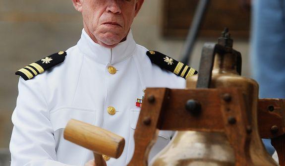 U.S. Navy veteran Paul Webb strikes the bell throughout the Memorial Day service, in Lynchburg, VA., Monday, May 27, 2013. (AP Photo/News & Daily Advance, Sam O'Keefe\)