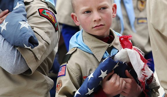 Jeremy Rivers of Boy Scout Troop 13 from St. Mary's Catholic Church holds a tattered American flag Monday, May 27, 2013, during a Memorial Day flag retirement ceremony at Sugarloaf Assisted Living in Winona, Minn. The troop retired nine American flags from the community by burning them in a ceremonial fire and later burying the ashes. (AP Photo/Winona Daily News, Andrew Link)