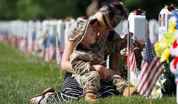 Brittany Jacobs kisses her son Chris near the grave site of her late husband, Christopher Jacobs, at Section 60 on Memorial Day at Arlington National Cemetery in Arlington, Virginia, Monday, May 27, 2013. Iraq and Afghanistan war veterans are buried in Section 60. (AP Photo/Molly Riley)
