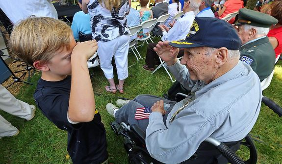 """Eight-year-old Jackson Turman of Woodstock, Ga., gives WWII Navy Veteran and Vietnam Veteran Frank Coleman, 85, Roswell, a salute during the """"Roswell Remembers"""" Memorial Day military ceremony at city hall on Monday, May 27, 2013, in Roswell, Ga. Coleman returns the salute. He also gave the young man a hug. Turman was attending the Memorial Day service with his grandfather Russ Johnson, of Roswell, who is a Marine Vietnam veteran.  (AP Photo/Atlanta Journal Constitution, Curtis Compton)"""