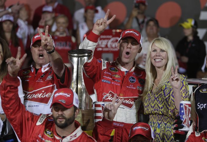 Kevin Harvick celebrates in victory lane with his wife Delana, right, after winning the NASCAR Sprint Cup series Coca-Cola 600 auto race at Charlotte Motor Speedway in Concord, N.C., Sunday, May 26, 2013. (AP Photo/Nell Redmond)