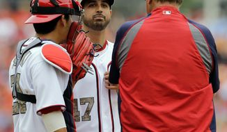 Washington Nationals catcher Kurt Suzuki, left, and pitching coach Steve McCatty, right, talk with starting pitcher Gio Gonzalez (47)during the fourth inning of an interleague baseball game against the Baltimore Orioles at Nationals Park Monday, May 27, 2013, in Washington. (AP Photo/Alex Brandon)