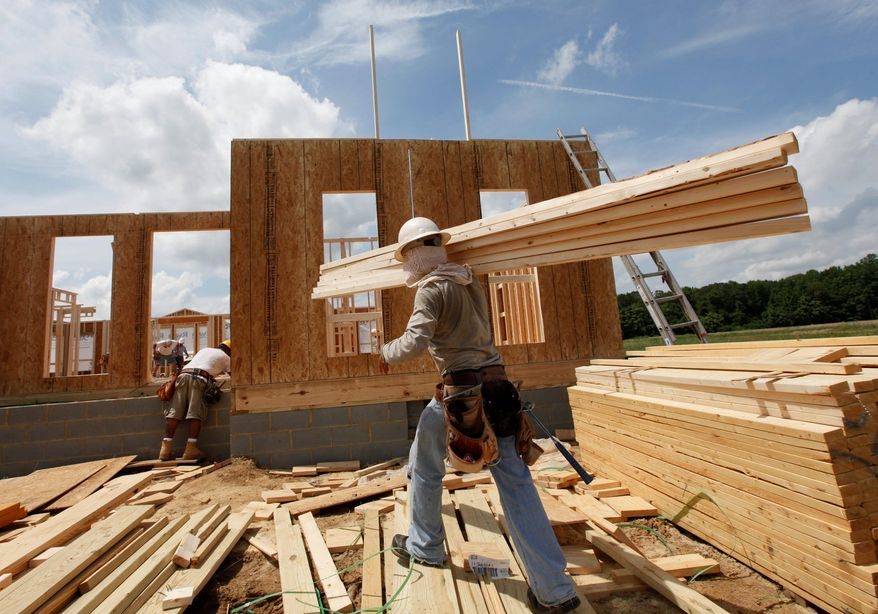 A construction worker carries a load of wood to a new home as workers frame the house in Chester, Va., on Wednesday, May 16, 2012. (AP Photo/Steve Helber)