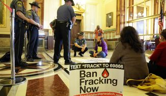 """**FILE** Illinois of Secretary of State Capitol police officers speak with protesters sitting in front of the entrance to Illinois Gov. Pat Quinn's office at the Illinois State Capitol in Springfield on May 23, 2013. The demonstrators were protesting against the state's oil drilling """"fracking"""" legislation. (Associated Press)"""