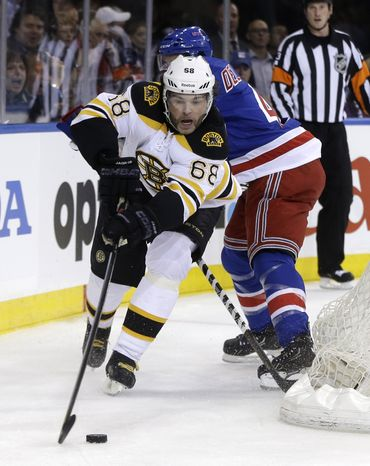 Boston Bruins' Jaromir Jagr, left, tries to shoot from behind the goal while New York Rangers' Michael Del Zotto defends during the first period in Game 3 of the NHL Eastern Conference semifinal hockey playoff series on Tuesday, May 21, 2013, in New York. (AP Photo/Seth Wenig)