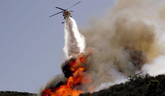 ** FILE ** A helicopter makes a water drop on a hotspot over a hill near Thousand Oaks, Calif. on Thursday, May 2, 2013. Authorities have ordered evacuations of a neighborhood and a university about 50 miles west of Los Angeles where a wildfire is raging close to subdivisions. (AP Photo/Nick Ut)