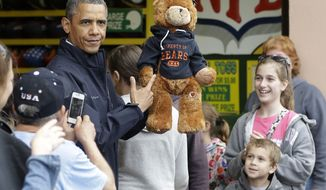 "President Obama holds up a stuffed bear that New Jersey Gov. Chris Christie (not shown) had won tossing a football after playing the ""Touchdown Fever"" game on the boardwalk during their visit to Point Pleasant, N.J.,  on May 28, 2013. Obama traveled to New Jersey to join Christie to inspect and tour the Jersey Shore's recovery efforts from Hurricane Sandy. (Associated Press)"