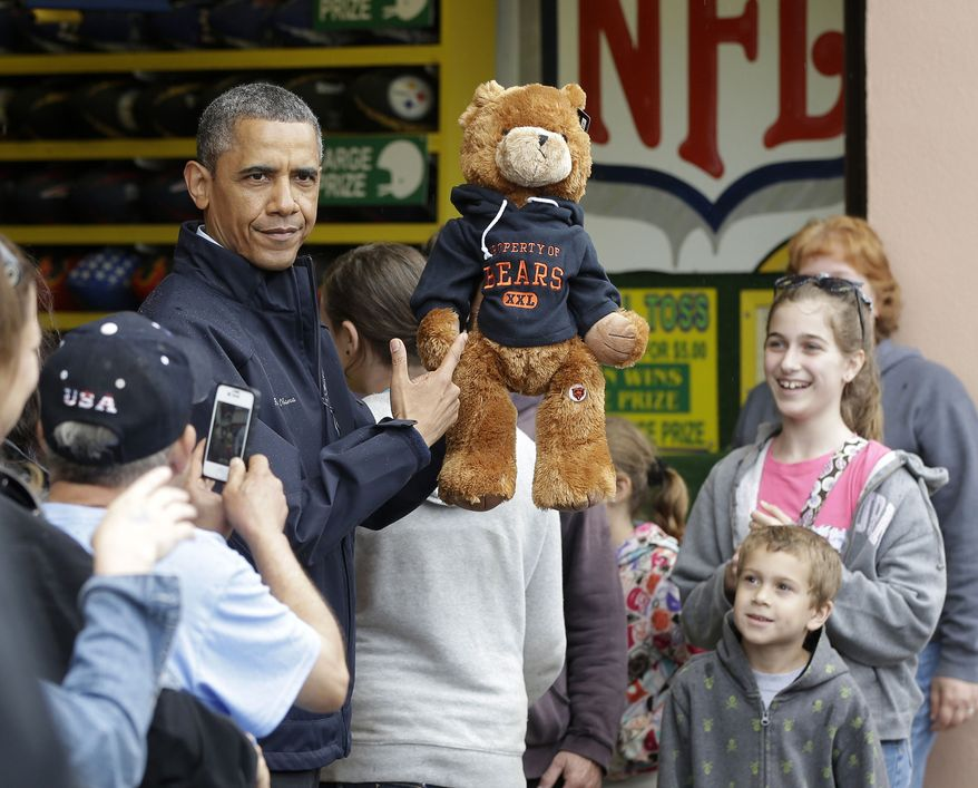 """President Obama holds up a stuffed bear that New Jersey Gov. Chris Christie (not shown) had won tossing a football after playing the """"Touchdown Fever"""" game on the boardwalk during their visit to Point Pleasant, N.J.,  on May 28, 2013. Obama traveled to New Jersey to join Christie to inspect and tour the Jersey Shore's recovery efforts from Hurricane Sandy. (Associated Press)"""