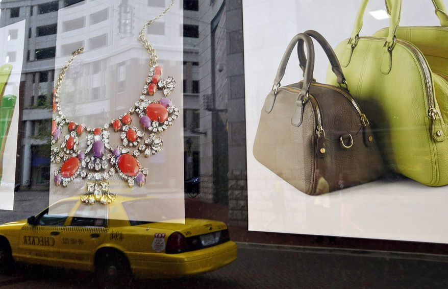 **FILE** Baltimore's Harbor East shopping district is reflected in a retail store's window display on April 24, 2013. (Associated Press)