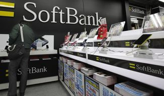 **FILE** A man looks at an iPad mini at an electronics store in Tokyo on Jan. 31, 2013. Japanese phone company Softbank, owned by billionaire Masayoshi Son said its net profit more than doubled in the October-December quarter from a year earlier, helped by strong sales of Apple's iPhone and iPads. (Associated Press)
