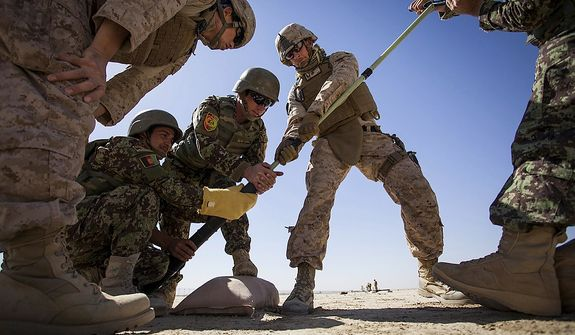 U.S. Marine Corps Staff Sgt. David Denseley, center, from Salt Lake City, Utah assists the Afghan National Army mortarmen clean out the bore of a 60mm mortar at a mortar range near Camp Shorabak, Helmand province, Afghanistan on May 4, 2013. (Credit: Staff Sgt. Ezekiel R. Kitandwe/U.S. Marine Corps)