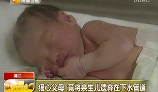 In this still image made from video from May 25, 2013, a baby who was rescued after being trapped in a sewage pipe just below a squat toilet in a public building, lies on a bed at a hospital in Jinhua city, eastern China. (AP Photo/Shaanxi TV via AP Video)