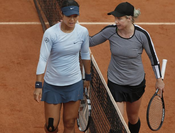 Bethanie Mattek-Sands of the U.S. pats 2011 Roland Garros winner Li Na of China on her shoulder after defeating Li Na in their second round match at the French Open tennis tournament, at Roland Garros stadium in Paris, Thursday, May 30, 2013. Mattek-Sands won in three sets 6-1, 5-7, 6-4. (AP Photo/Michel Spingler)