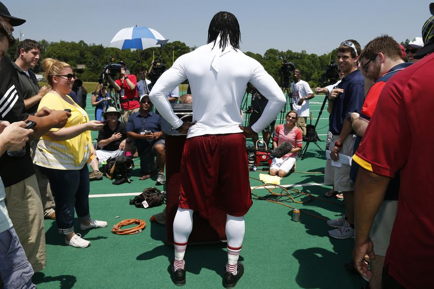 Washington Redskins quarterback Robert Griffin III, center, speaks to reporters after a NFL football practice at Redskins Park in Ashburn, Va., Thursday, May 30, 2013. (AP Photo/Charles Dharapak)