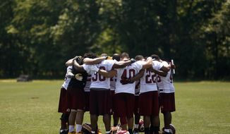 Members of the Washington Redskins offense huddle in prayer after NFL football practice at Redskins Park in Ashburn, Va., Thursday, May 30, 2013. (AP Photo/Charles Dharapak) ** FILE **