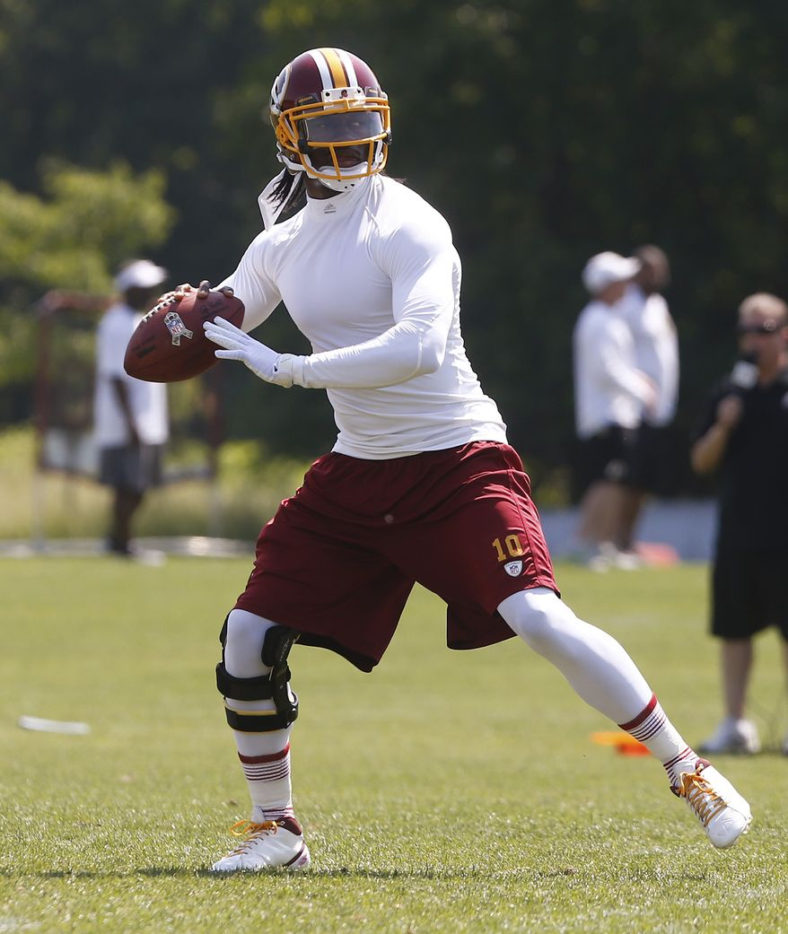 Washington Redskins quarterback Robert Griffin III (10) practices during an NFL football organized team activity at Redskins Park in Ashburn, Va., Thursday, May 30, 2013. (AP Photo/Charles Dharapak)