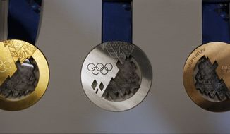 Gold, left, silver, center, and bronze medals are displayed for journalists during a presentation of Sochi 2014 Olympic medals at the SportAccord International Convention in St. Petersburg, Russia, Thursday, May 30, 2013. (AP Photo/Dmitry Lovetsky)