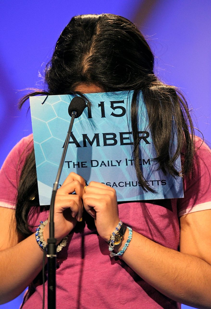 """Amber Born, 14 of Marblehead, Mass., covers her face while spelling """"malacophilous"""" during the semifinal round of the Scripps National Spelling Bee in Oxon Hill, Md., Thursday, May 30, 2013. (AP Photo/Cliff Owen)"""
