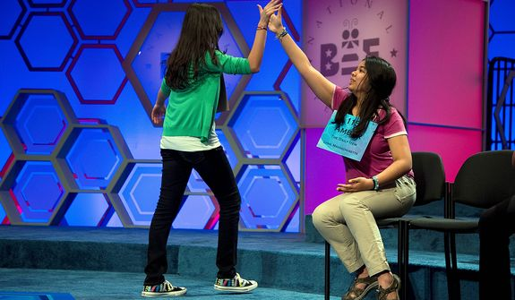 "Vismaya Kharkar, 14, of Bountiful, Utah, left, is congratulated by Amber Born, 14 of Marblehead, Mass., after spelling the word ""agelicism"" correctly during the semifinal round of the National Spelling Bee on Thursday, May 30, 2013, in Oxon Hill, Md. (AP Photo/Evan Vucci)"
