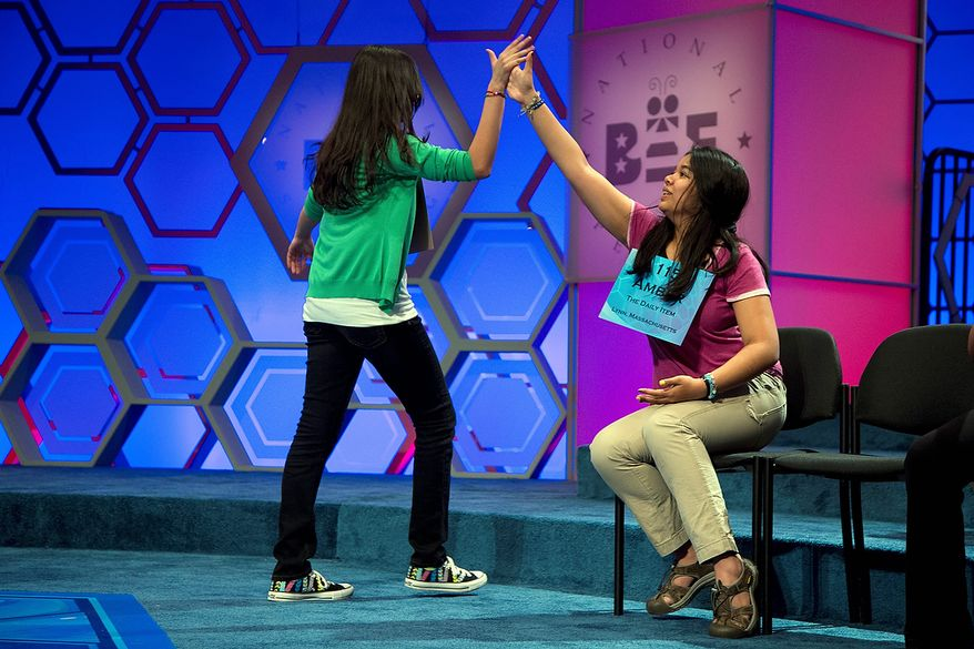 """Vismaya Kharkar, 14, of Bountiful, Utah, left, is congratulated by Amber Born, 14 of Marblehead, Mass., after spelling the word """"agelicism"""" correctly during the semifinal round of the National Spelling Bee on Thursday, May 30, 2013, in Oxon Hill, Md. (AP Photo/Evan Vucci)"""