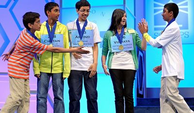 Sriram Hathwar, 13 of Painted Post, N.Y., left, reaches out to shake hands with Syamantak Payra, 12, of Friendswood, Texas, right, as he high-fives Vismaya Kharkar, 14, of Bountiful, Utah, as Chetan Reddy, 13 of Plano, Texas, yellow shirt, and Arvind Mahankali, 13, of Bayside Hills, N.Y., center, watch after they learned that they will advance to the final round of the Scripps National Spelling Bee in Oxon Hill, Md., Thursday, May 30, 2013. (AP Photo/Cliff Owen)