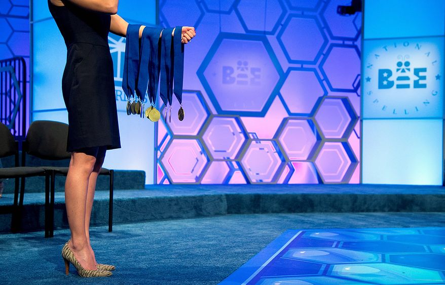 Janice Liebenberg, National Spelling Bee Sponsorship and Operations Coordinator, holds the finalist medals before the announcement of National Spelling Bee finalists on Thursday, May 30, 2013, in Oxon Hill, Md. (AP Photo/Evan Vucci)