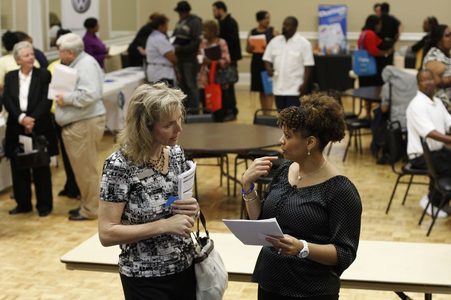 Donna Van Natten (left) with the Enterprise Center and Valoria Armstrong with the Tennessee American Water Co. converse during a job fair at the Urban League in Chattanooga, Tenn., on Tuesday, April 30, 2013. (AP Photo/Chattanooga Times Free Press, Dan Henry)