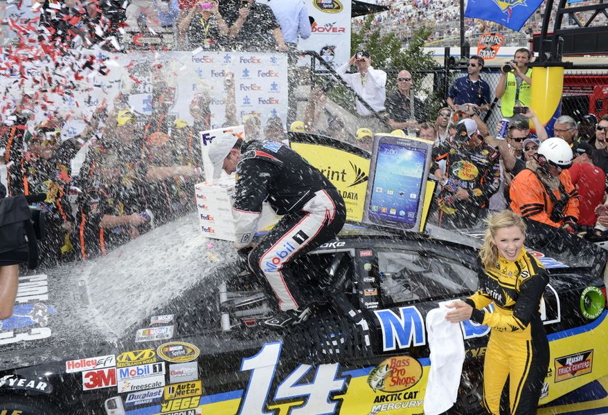 Tony Stewart is showered as he climbs out of the car to celebrate in Victory Lane after winning the NASCAR Sprint Cup Series auto race, Sunday, June 2, 2013, at Dover International Speedway in Dover, Del. (AP Photo/Nick Wass)