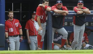 Washington Nationals' Chad Tracy (18), Ryan Zimmerman (11), Rick Eckstein, and manager Davey Johnson, right, watch the final moments of a baseball game against the Atlanta Braves, Sunday, June 2, 2013, in Atlanta. Atlanta won 6-3. (AP Photo/John Amis)